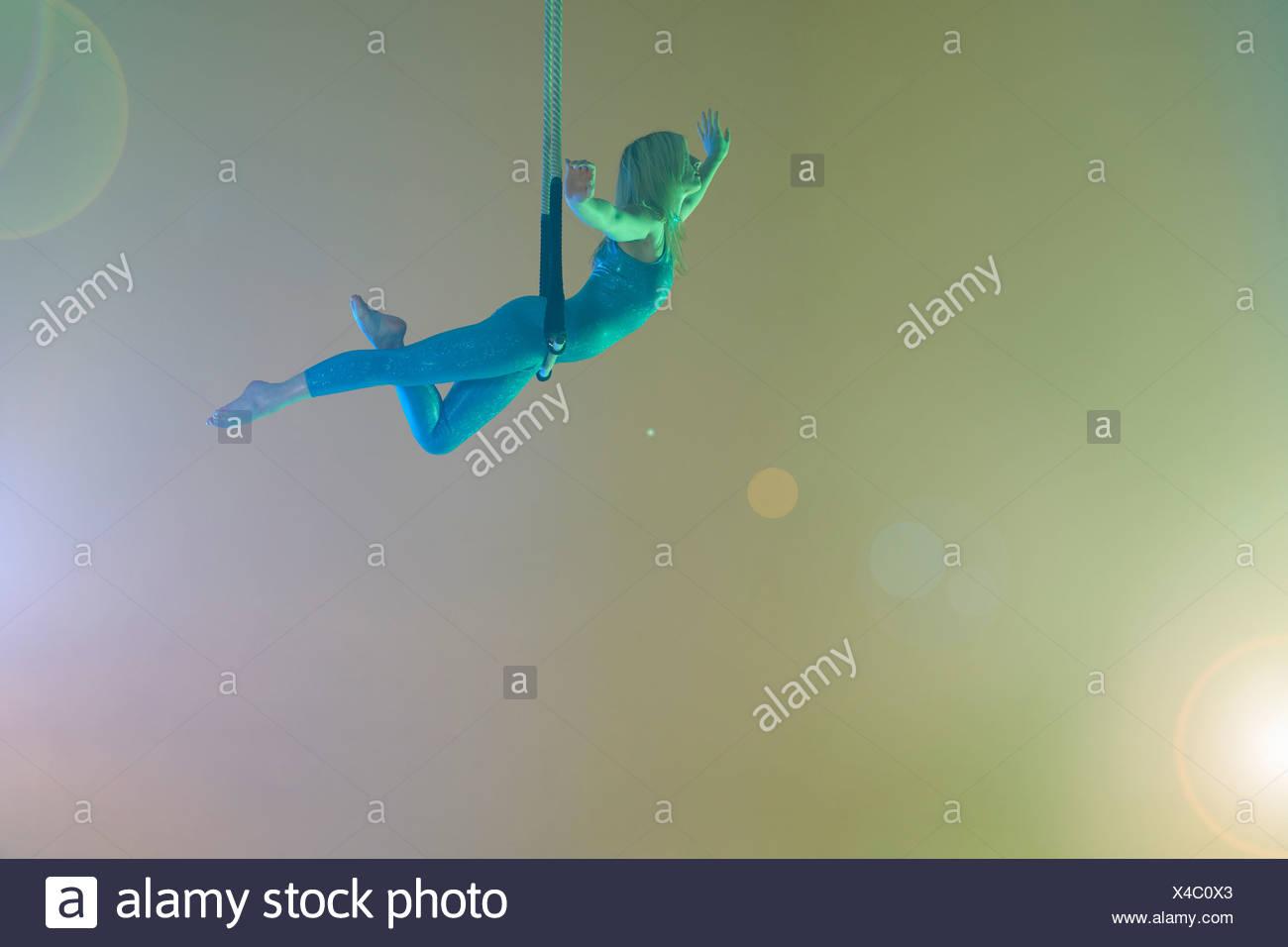 Trapeze artist balancing on trapeze Stock Photo