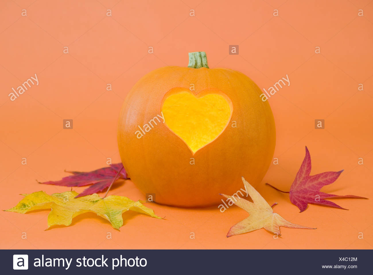 Pumpkin with heart-shape lit from inside - Stock Image