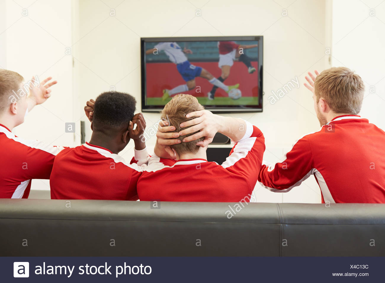 Group Of Sports Fans Watching Game On TV At Home - Stock Image
