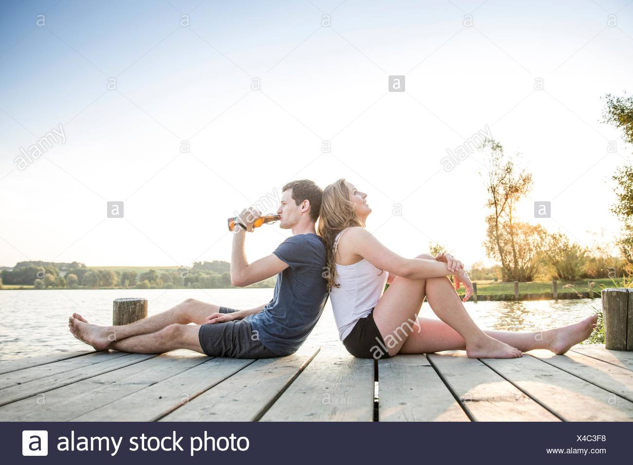 Young couple relaxing on jetty, sitting back to back - Stock Image