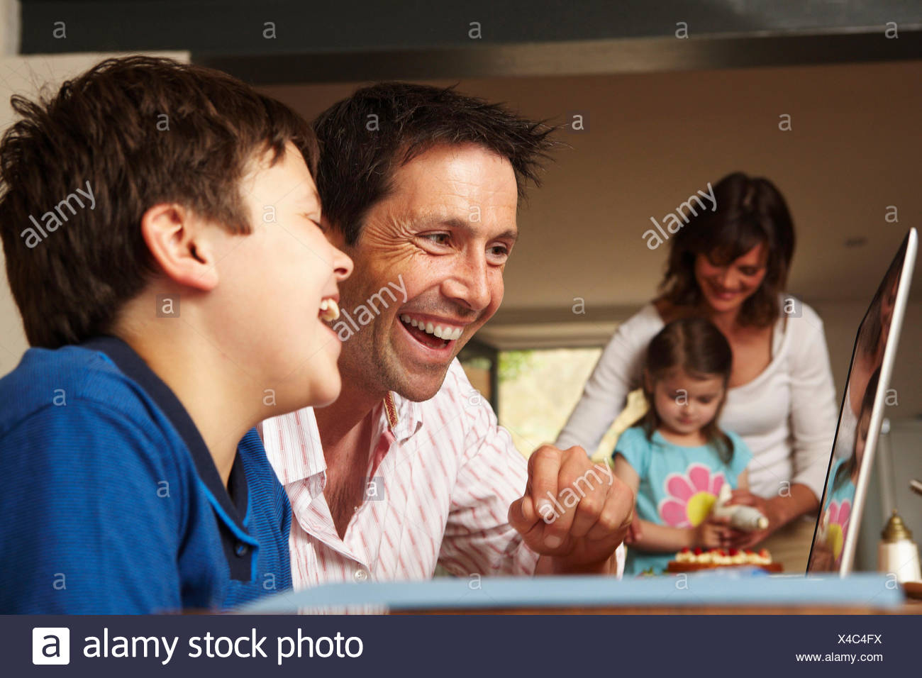 A family, two parents and two children together at home. A father and son on a laptop, and mother and daughter icing a cake. - Stock Image