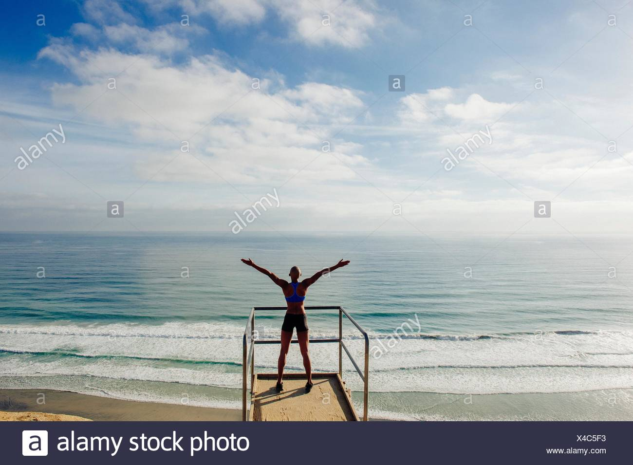 Young woman standing on look out point beside sea, arms raised, rear view - Stock Image