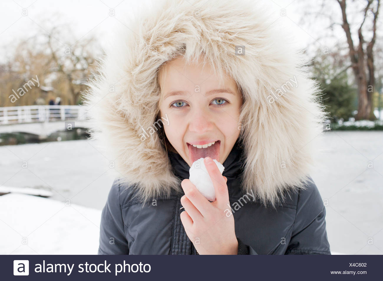 Girl in fur hood licking snow - Stock Image