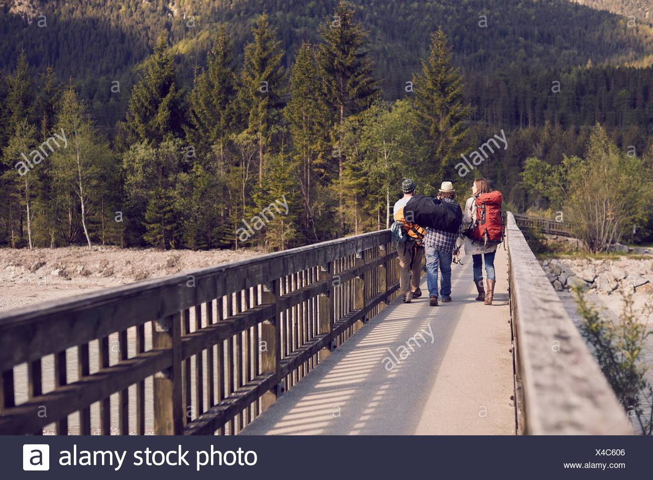 Rear view of three people walking to mountains wearing backpacks - Stock Image