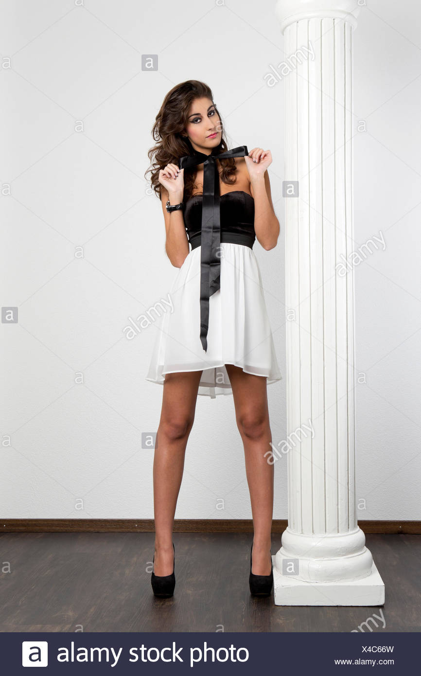 fbc08e28e4 Young woman with black top, short white skirt and black high heels posing  with a