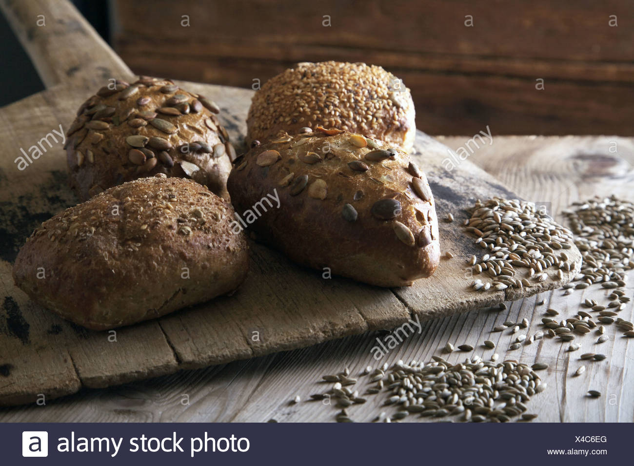 Rye bread rolls on an old bread slide with rye grains - Stock Image