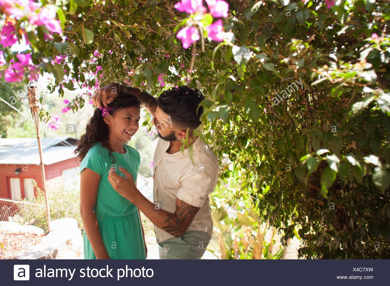 Mid adult man placing flower blossom in daughters hair - Stock Image