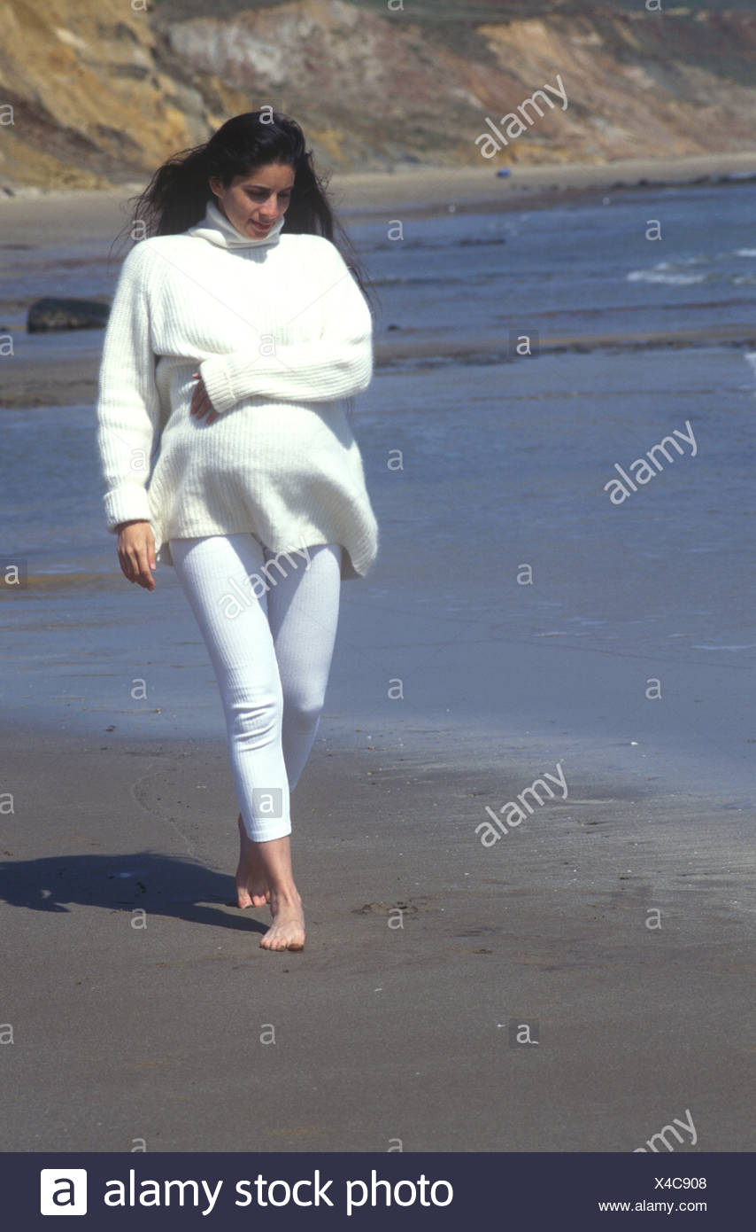 mixed race heavily pregnant woman walking on the beach warmly dressed in a white jumper - Stock Image