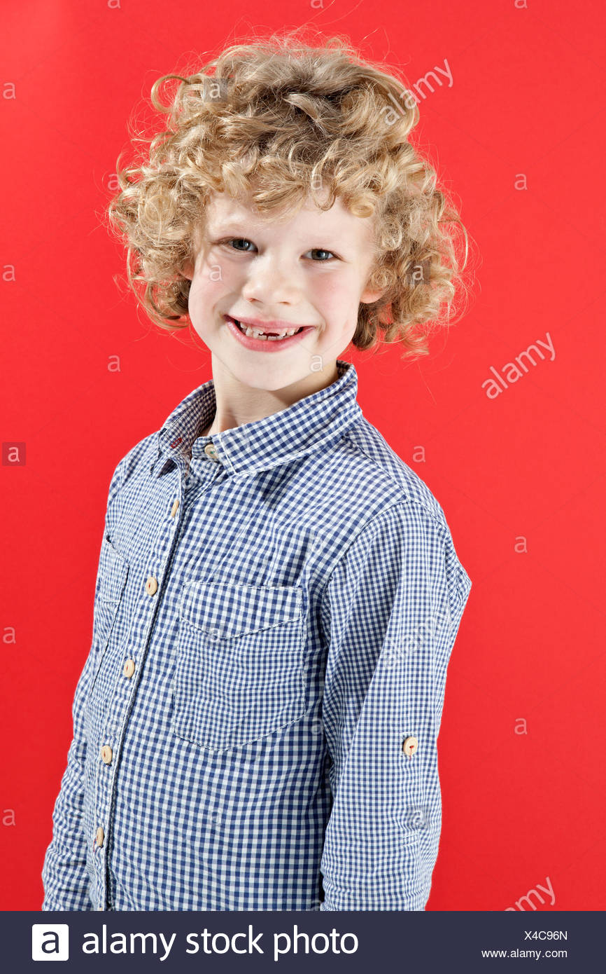 A boy with tousled curly blond hair smiling at the camera - Stock Image