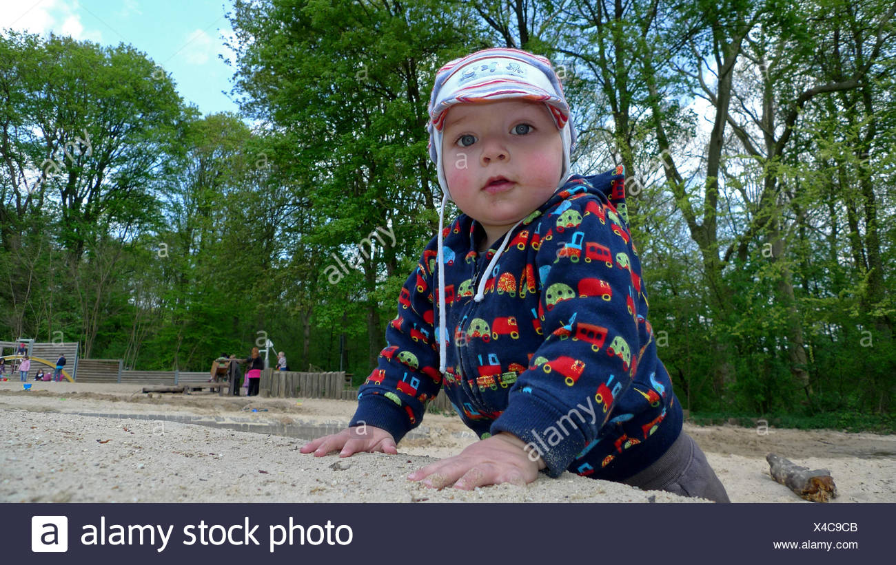 little boy playing in sandbox on playground - Stock Image