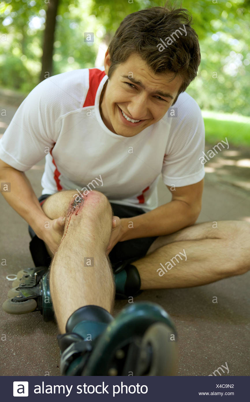 Skater injured and clutching leg - Stock Image