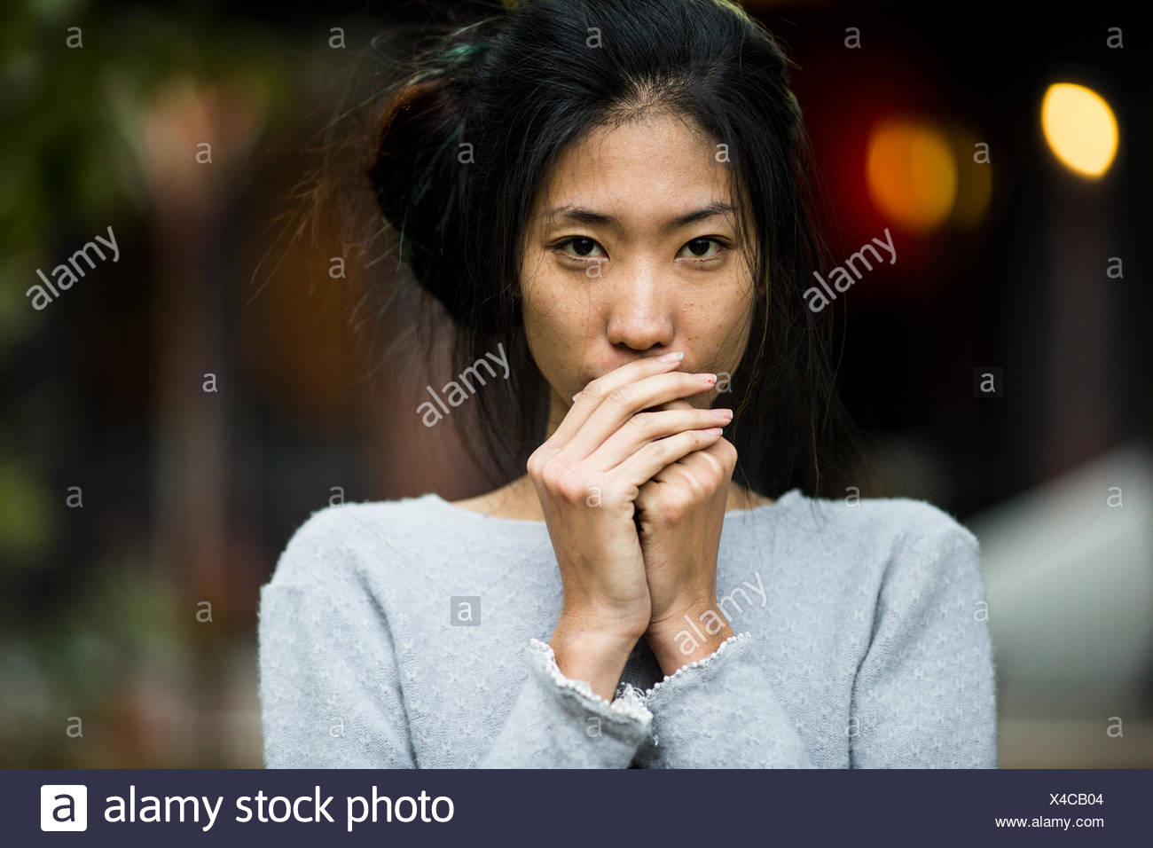 A young, pretty Asian woman in a garden in Hanoi, Vietnam. - Stock Image