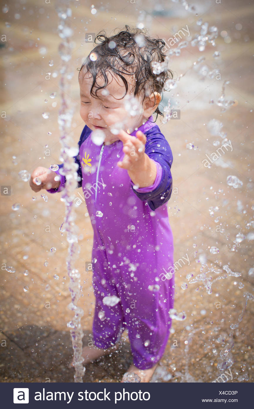 Cute baby girl with eyes closed getting sprinkled with water - Stock Image