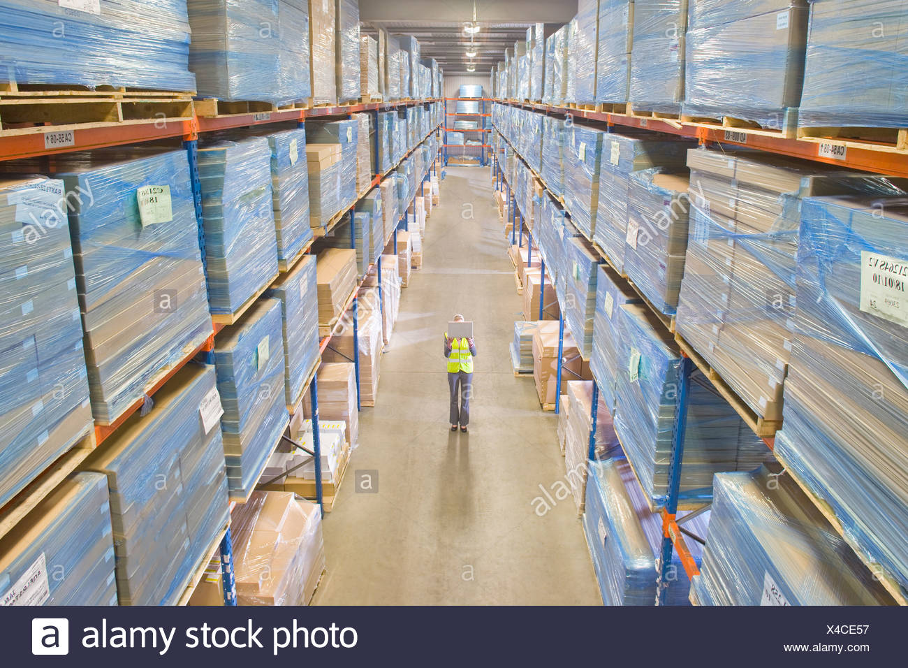 Warehouse manager holding laptop in aisle - Stock Image