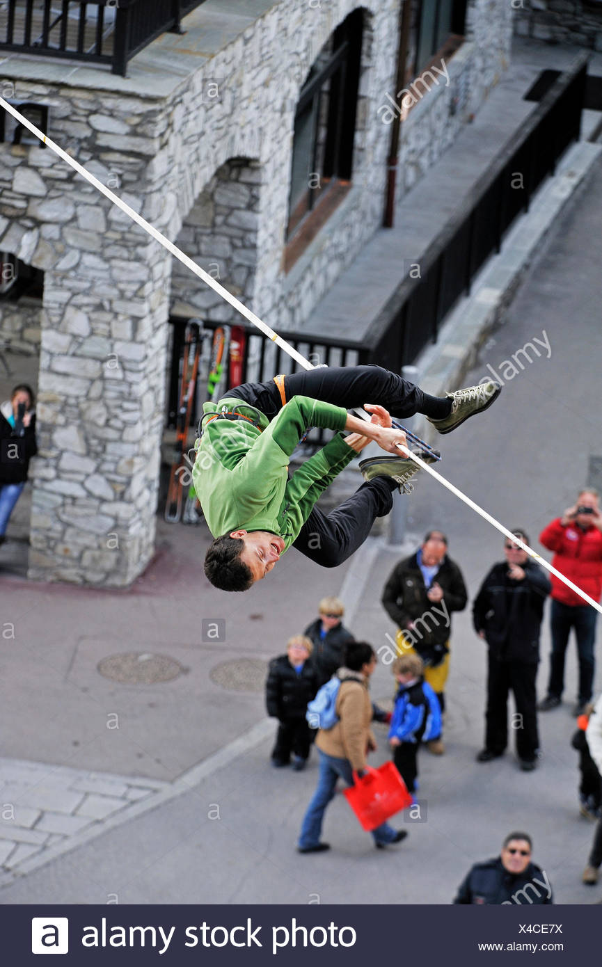 man on a highline slackline over an alley loosing balance, France, Savoie, Val-d�Is�re - Stock Image