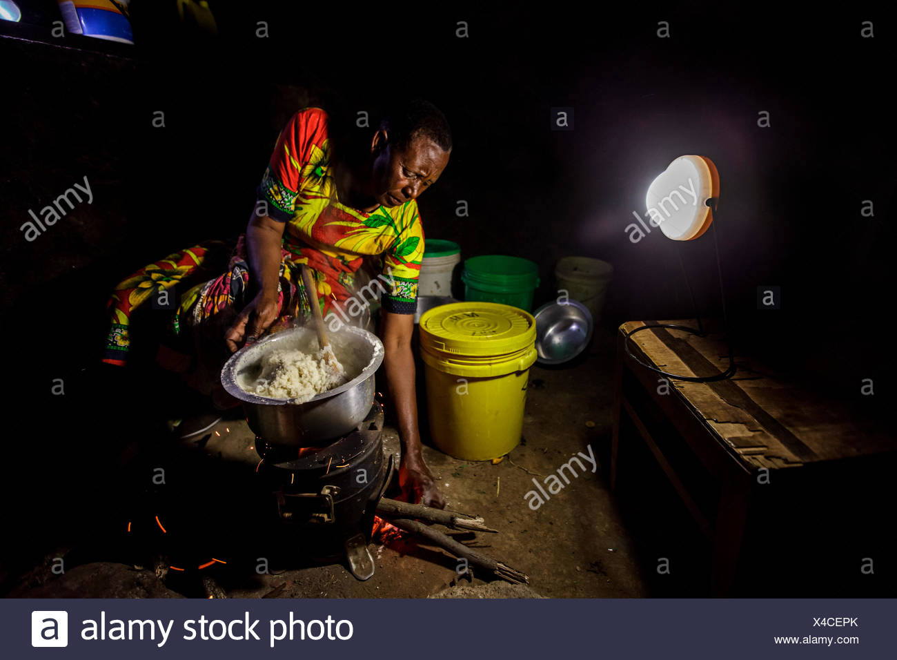 At her home near Arusha, Tanzania Solar Sister entrepreneur Julieth Mollel prepares a dinner of ugali, vegetables and beans cooking on her clean cookstove. Ugali is a staple eaten in many countries in Africa and is cornmeal porridge. Working in her compact outdoor kitchen at night is easier now both with the clean cookstove that puts out very little smoke and uses only a fraction of the firewood of a traditional three-stone cookstove but also with her Solar Sister solar lantern to light up the area brightly while she works. - Stock Image
