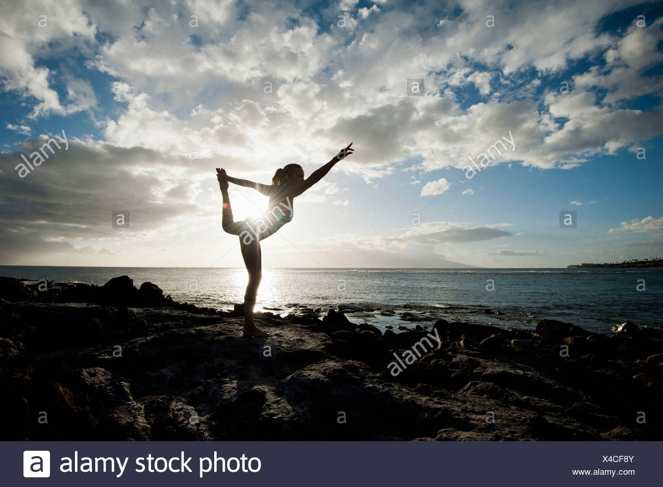 Woman practicing yoga on rock formation - Stock Image