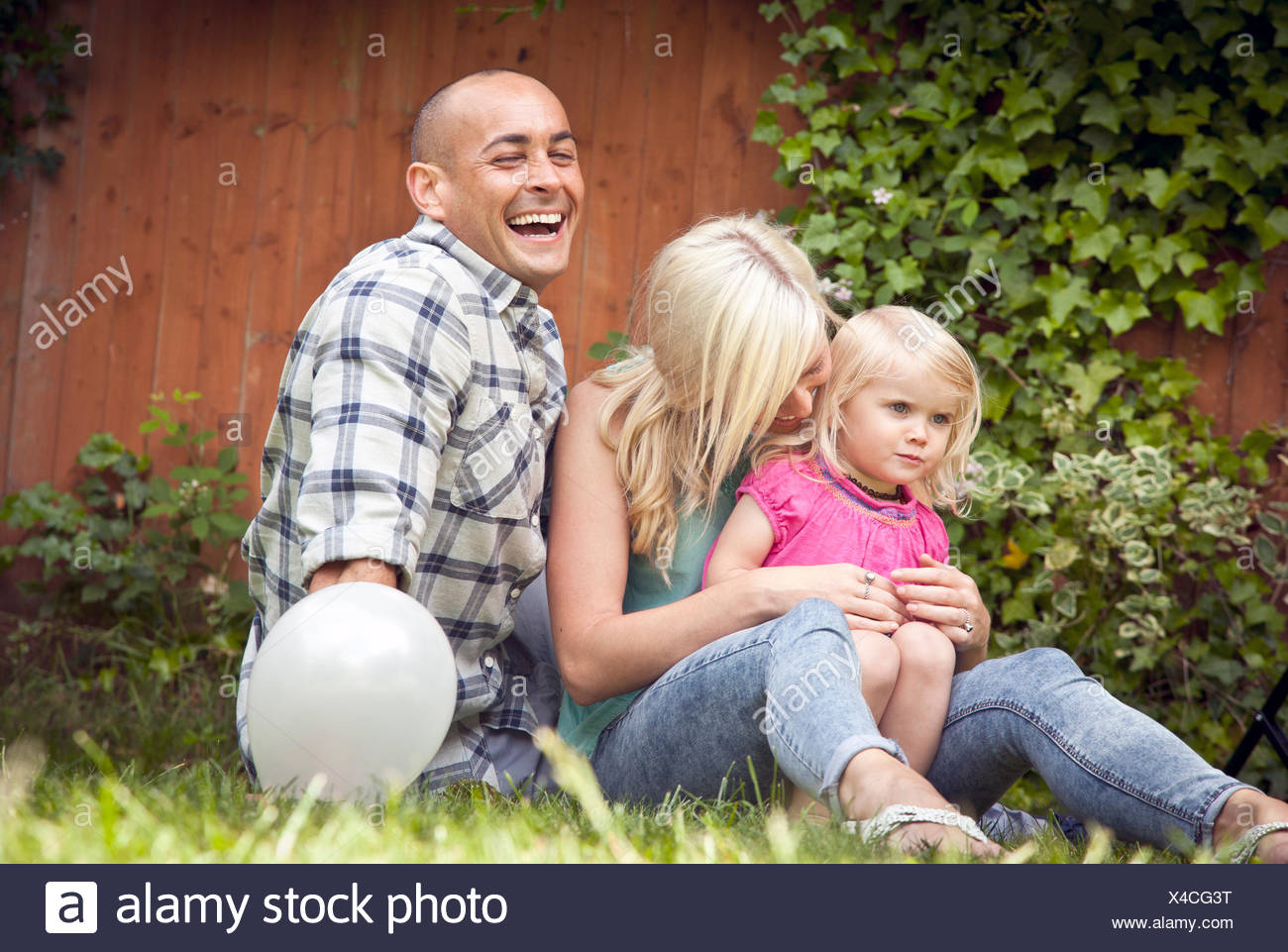 Happy couple sitting with toddler daughter in garden - Stock Image