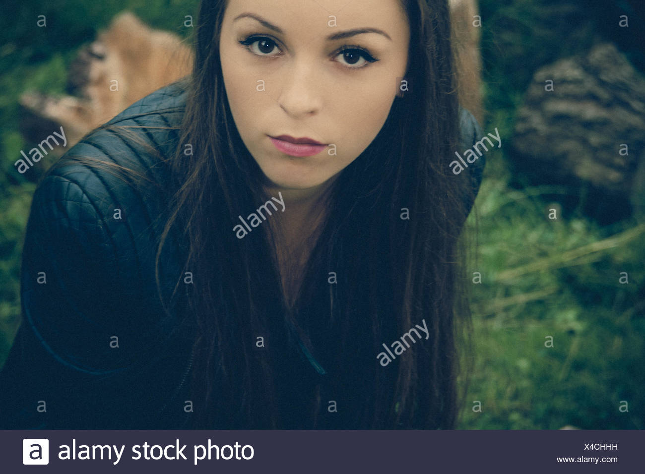 Portrait Of Beautiful Young Woman Wearing Black Leather Jacket In Forest - Stock Image
