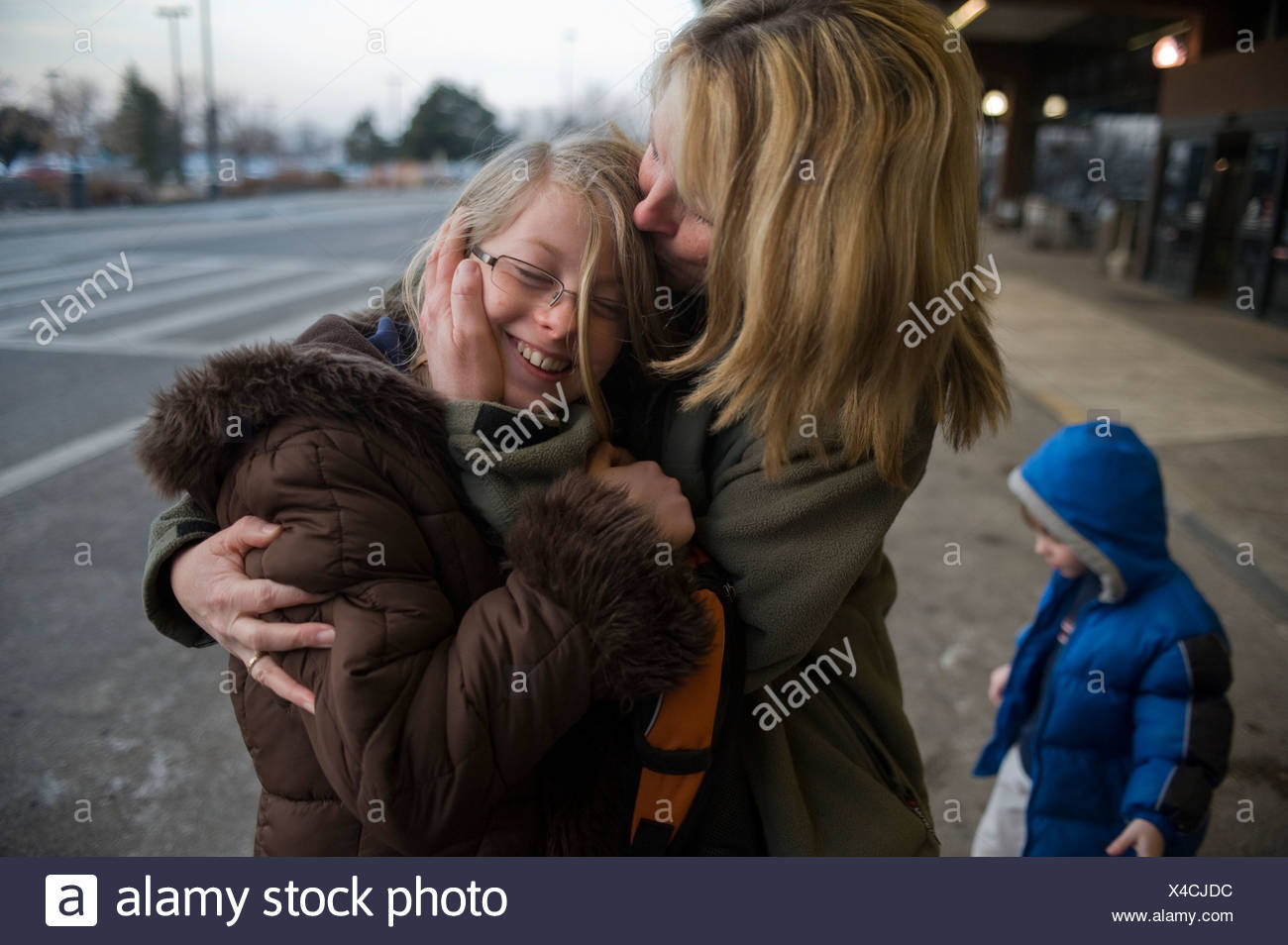 A woman is greeted by her daughter after a long trip. - Stock Image
