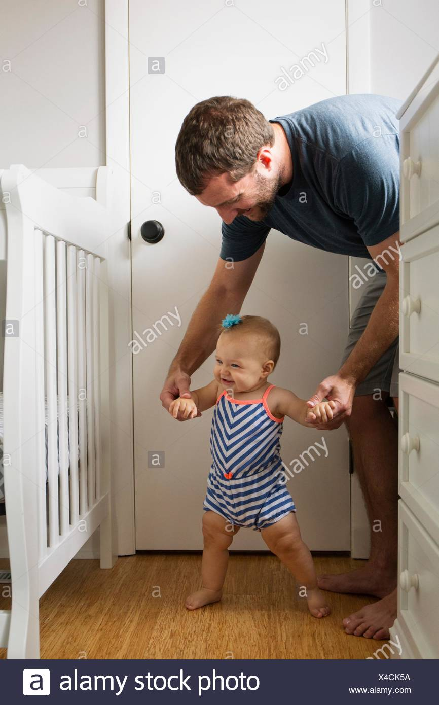 Mid adult man holding baby daughter hands whilst toddling in nursery - Stock Image