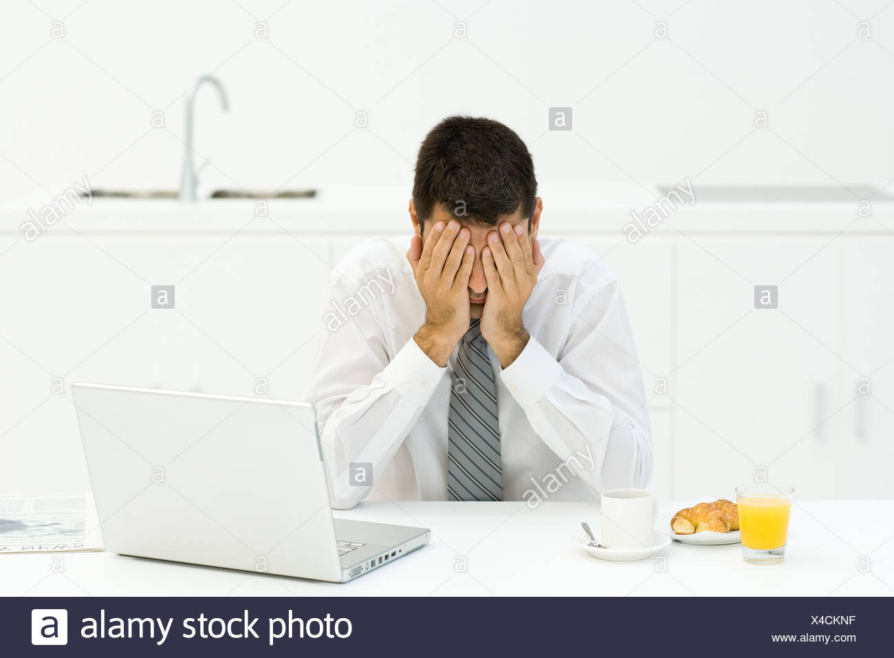 Man sitting next to breakfast and laptop, covering face with hands - Stock Image
