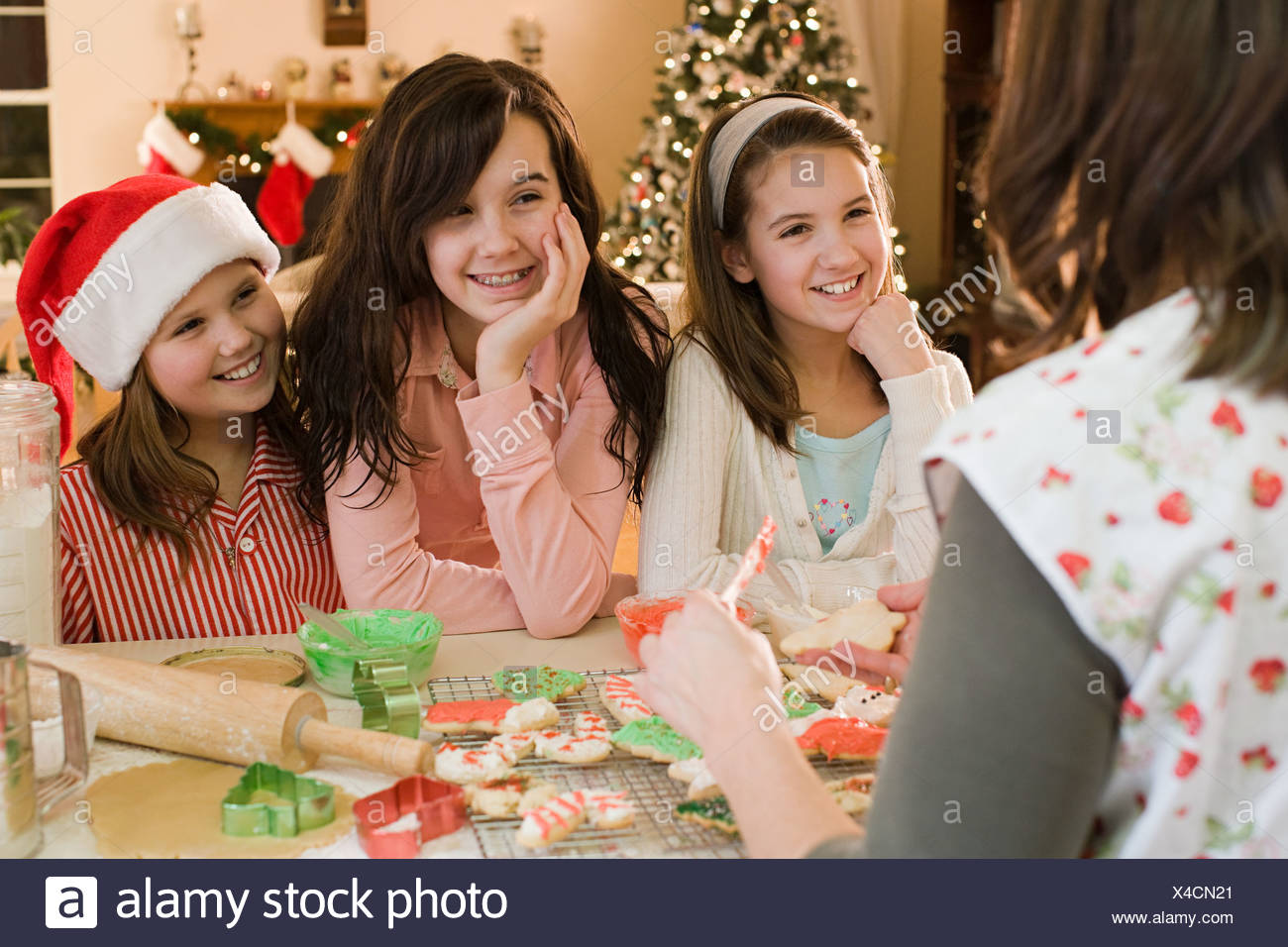 Girls and mother making cookies - Stock Image