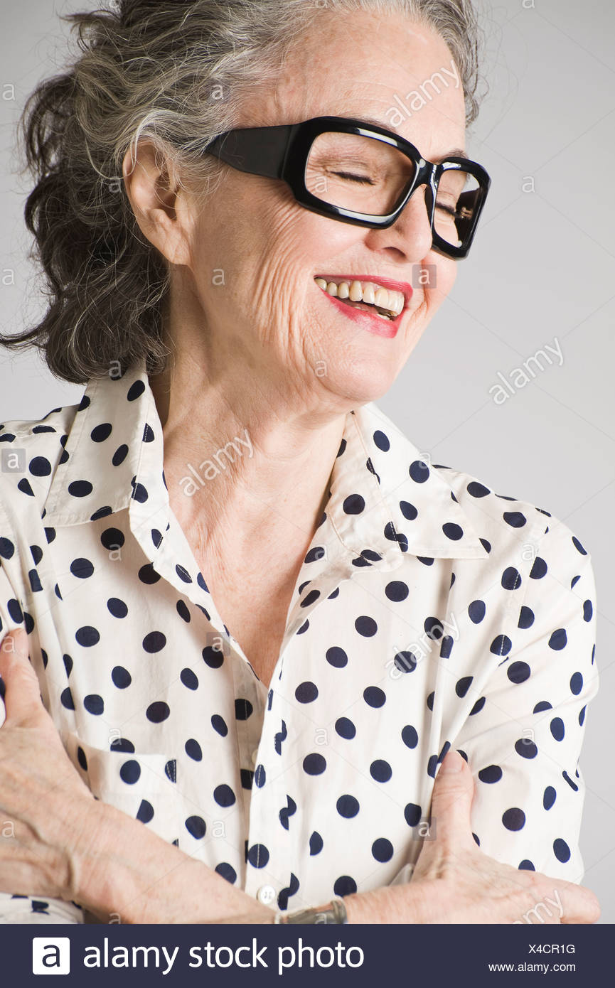 Portrait of senior woman, arms crossed, laughing - Stock Image