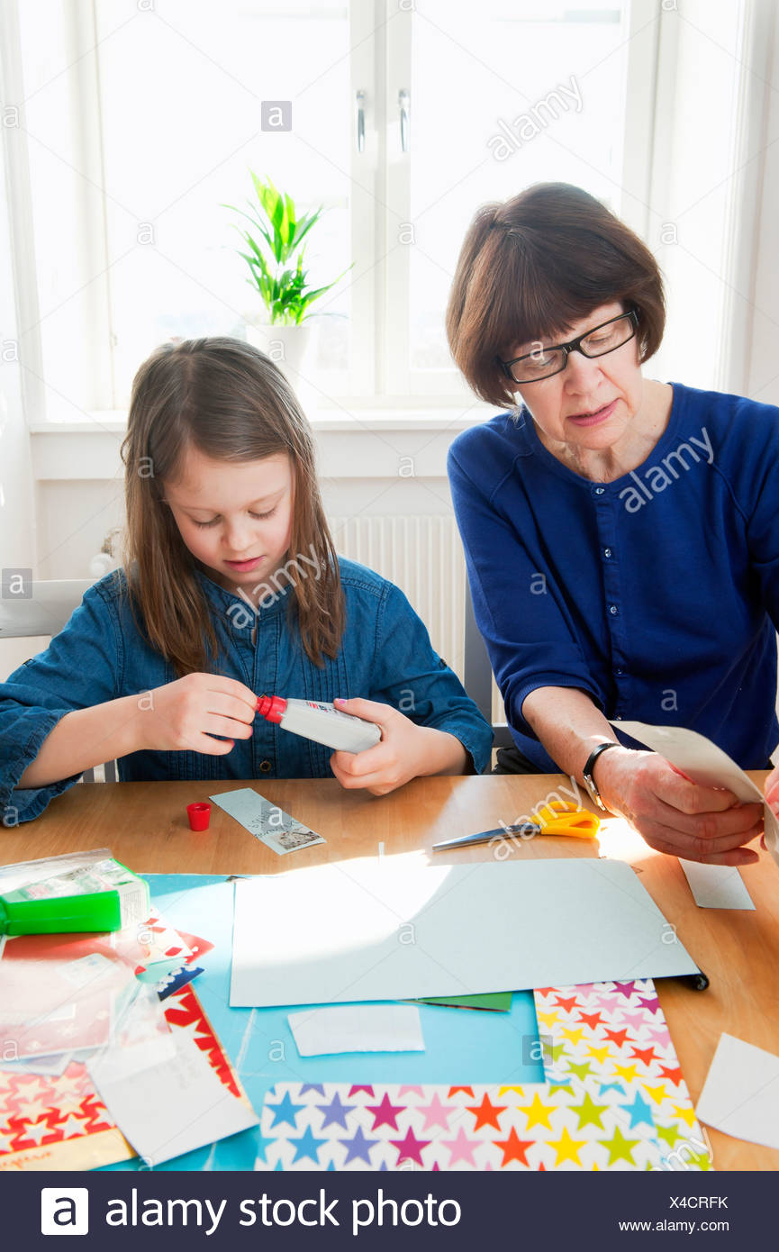 Grandmother doing handicrafts with granddaughter (6-7) - Stock Image