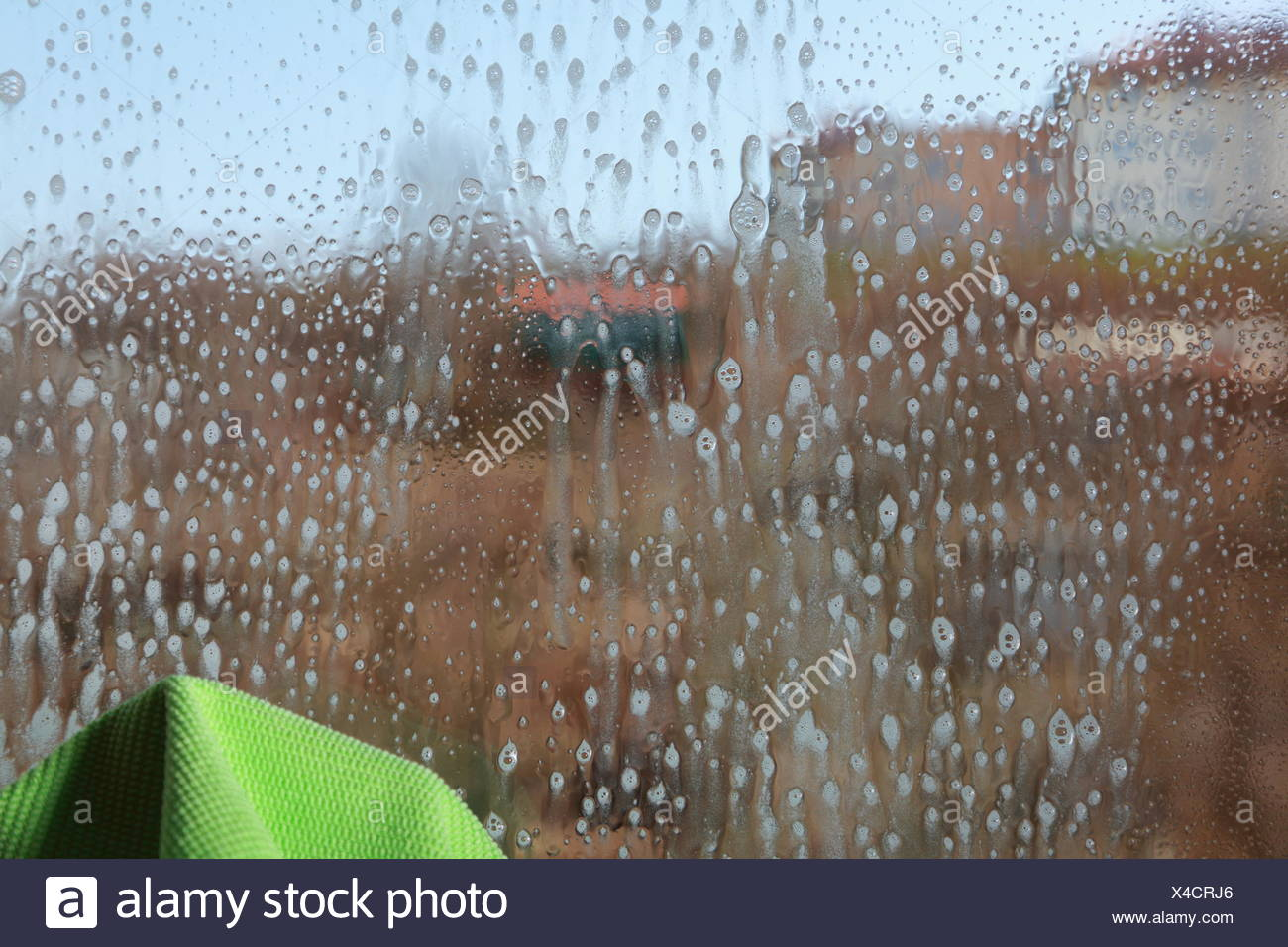 Drops on the windowpane, cleaning window with spray