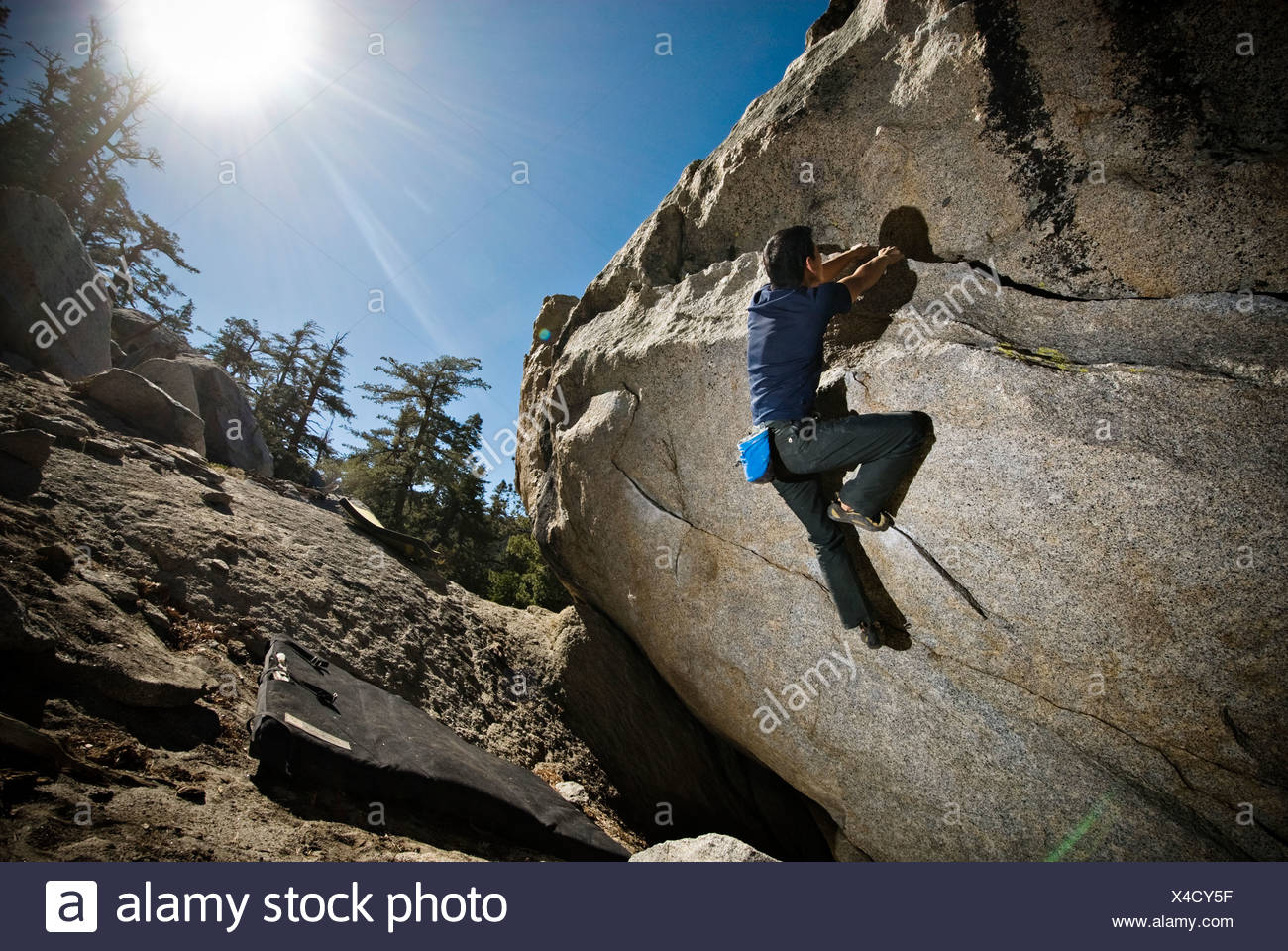 An Asian-American man rock climbs a boulder problem at The Tramway, Palm Springs, CA. Stock Photo
