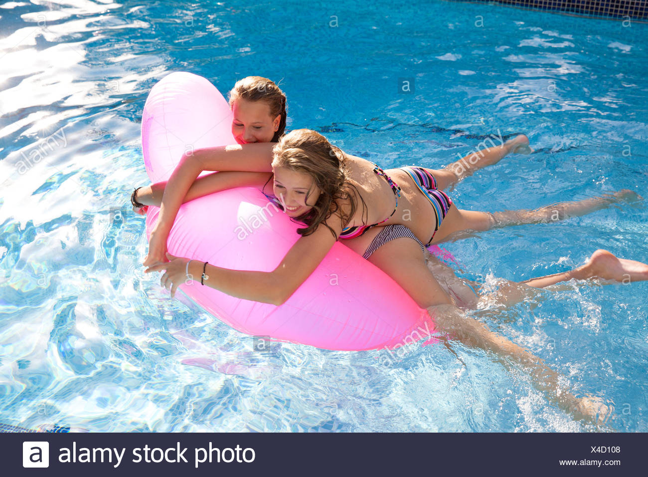 Two teenage girls holding onto air bed in swimming pool Stock Photo