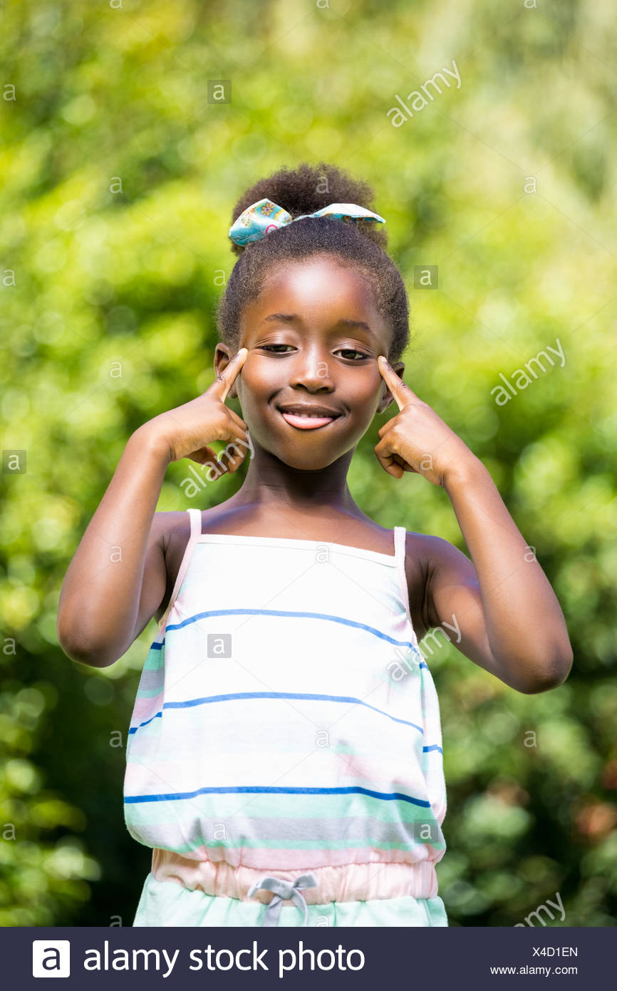 Mixed-race girl grimacing face to the camera - Stock Image