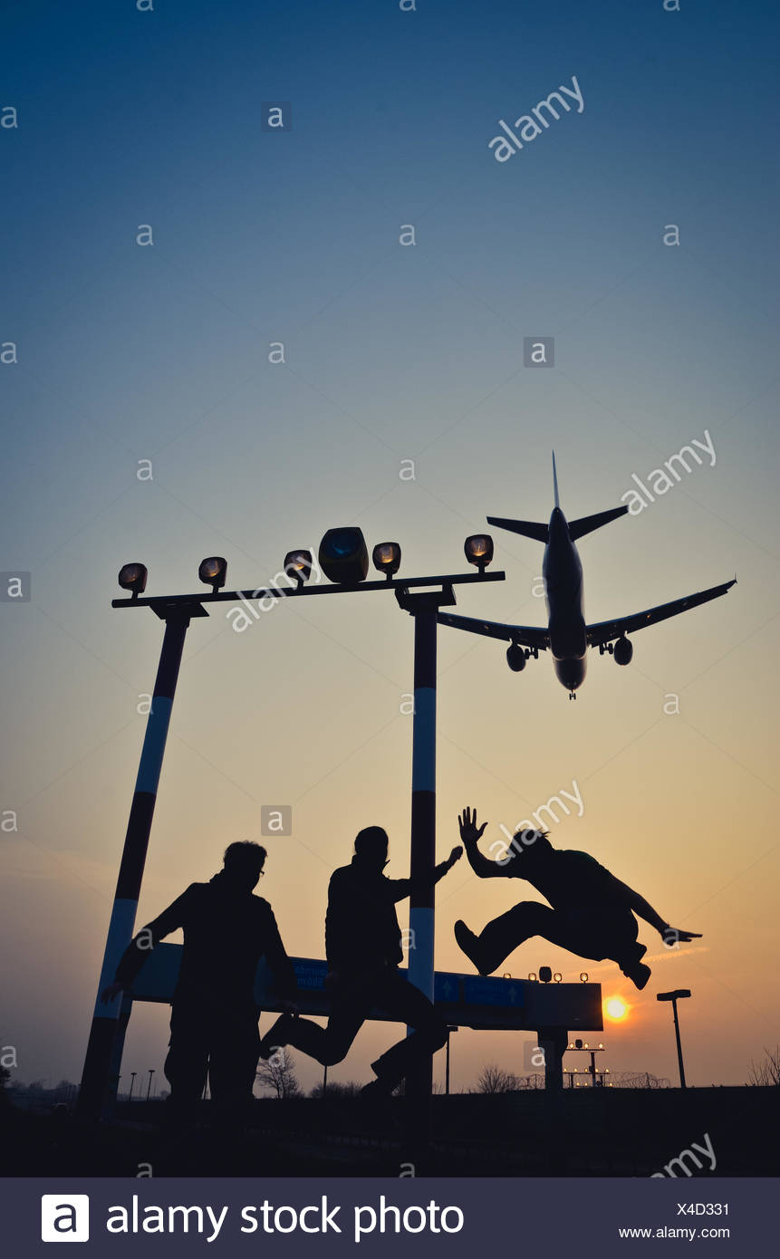 Friends Enjoying With Airplane Flying Against Sky - Stock Image