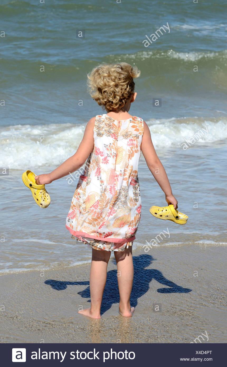 Kleines Mädchen am Strand sieht auf die Wellen, Skagen, Jutland, Denmark - Stock Image