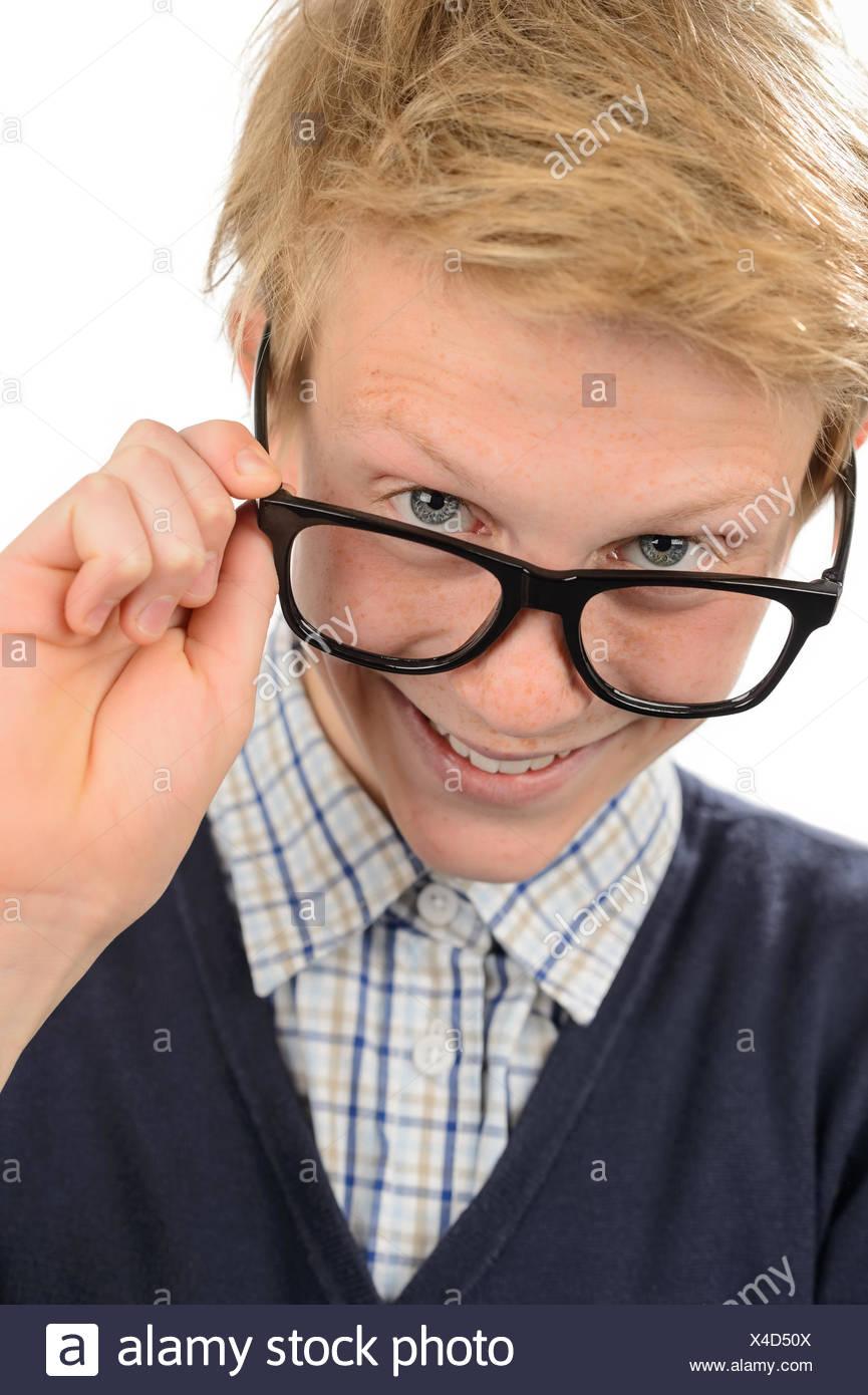 Cheerful nerd boy looking above geek glasses - Stock Image