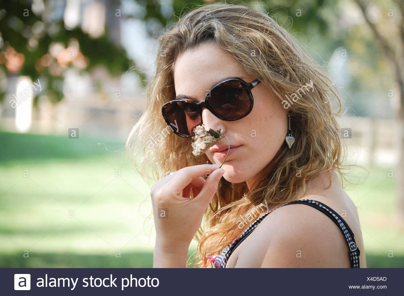 Portrait of young woman smelling flower - Stock Image