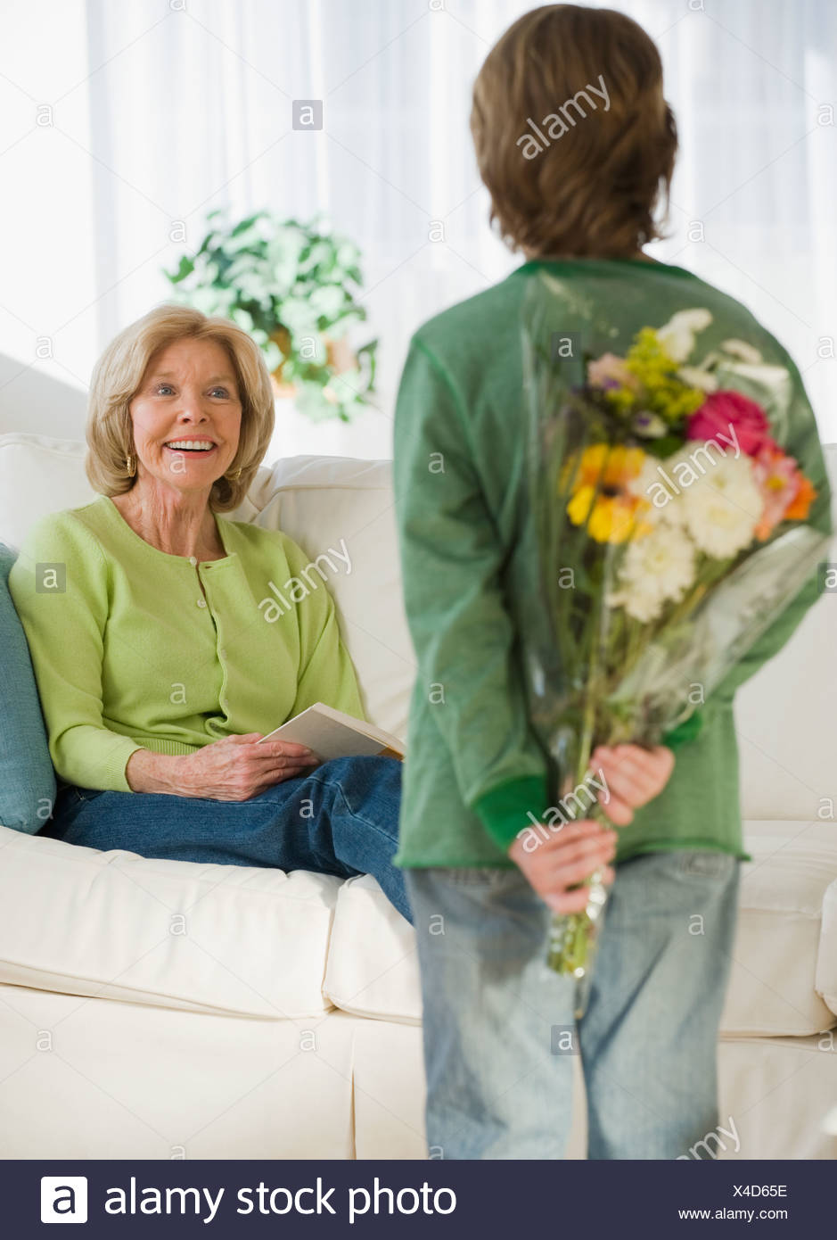 Grandson surprising grandmother with flowers Stock Photo