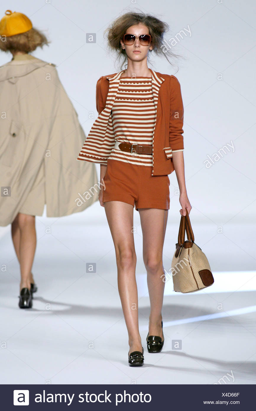 Brown Tones: Two piece shorts suit and matching striped top, belt, brown shades, handbag and patent loafers - Stock Image
