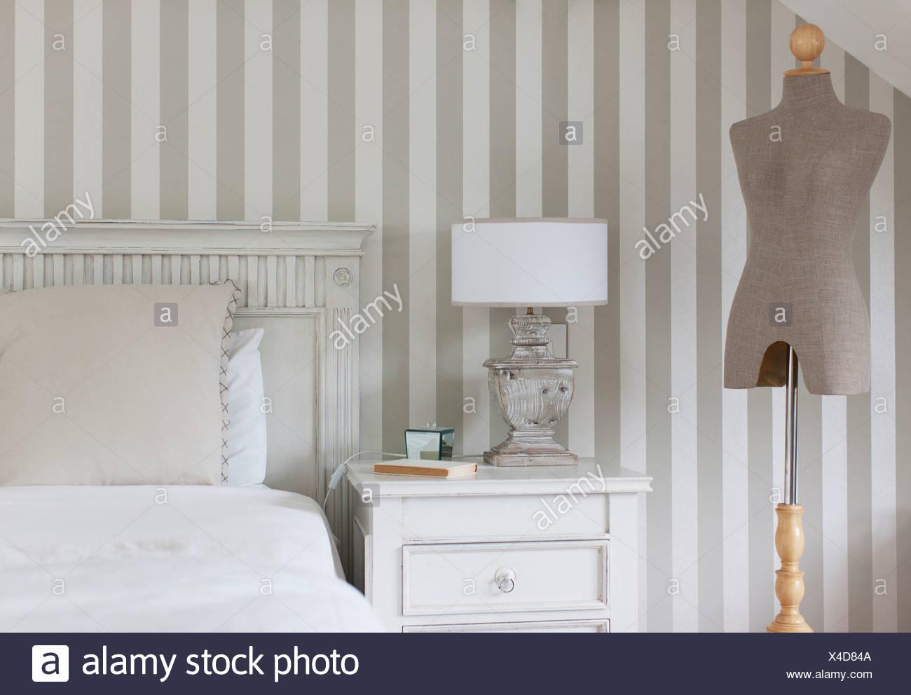 Dressmakers model and bed in feminine bedroom - Stock Image
