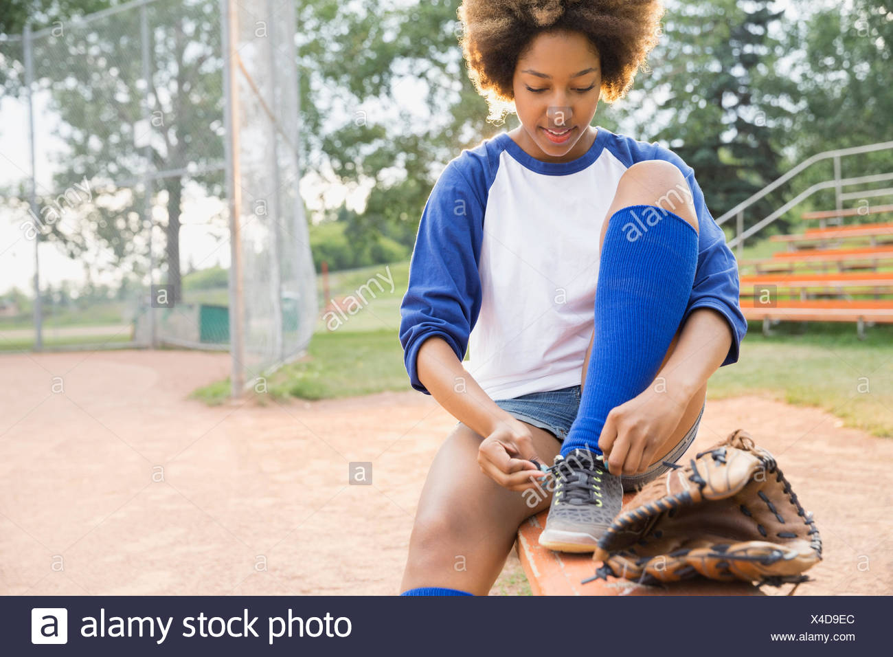 Baseball player tying shoe on field - Stock Image