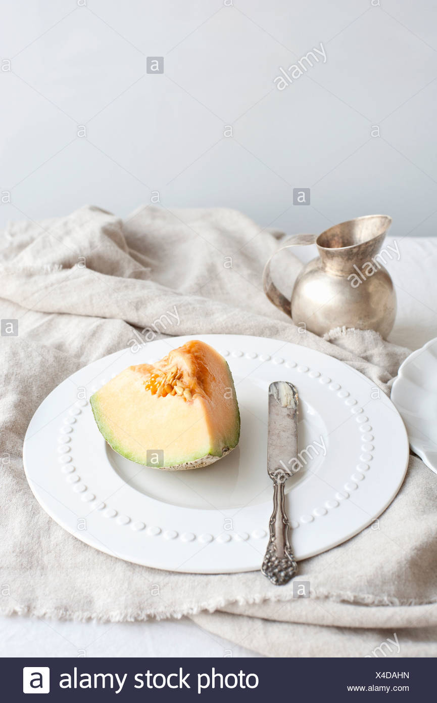 Plate of melon with butter knife - Stock Image