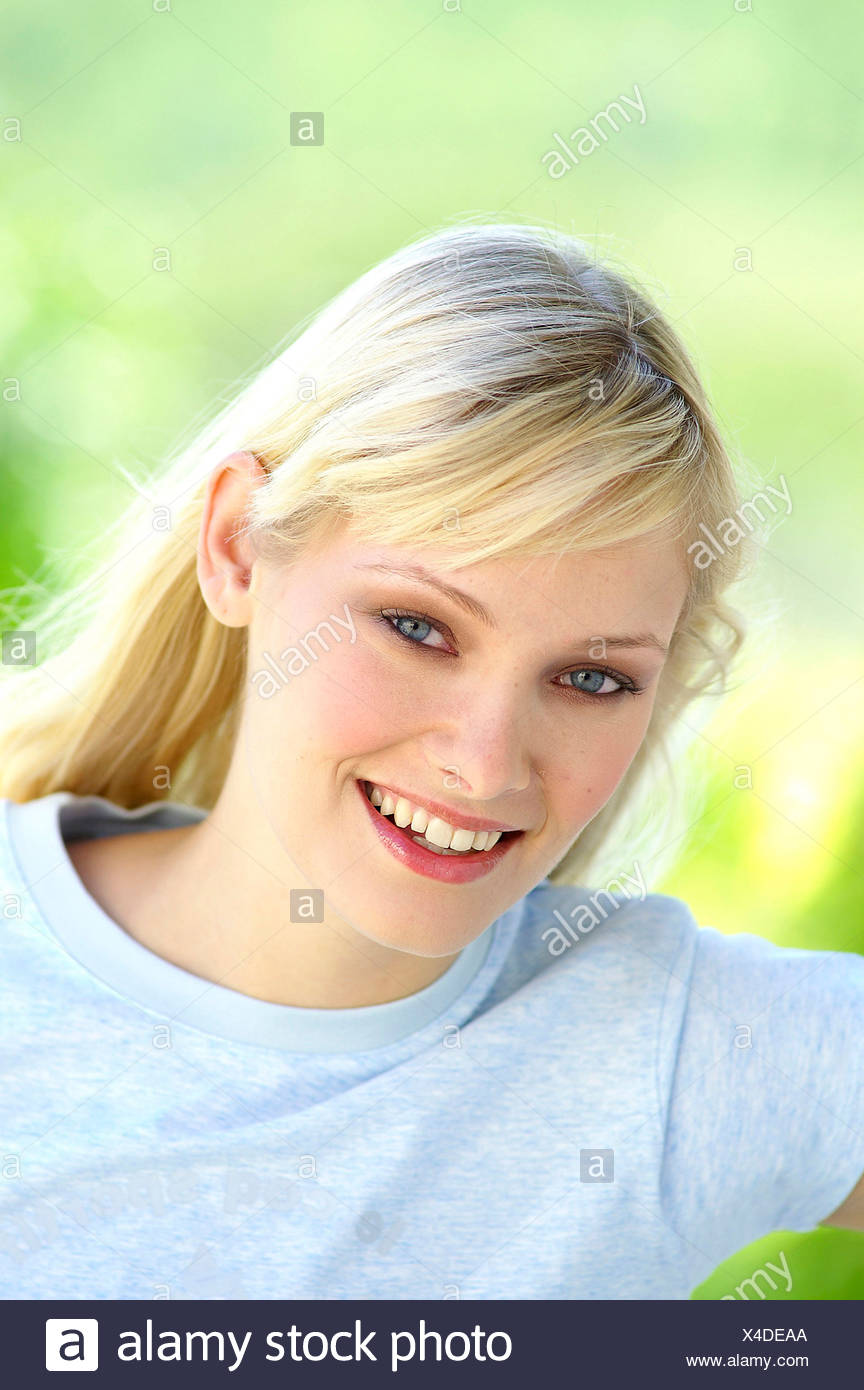 Female long straight blonde hair tucked behind ear wearing pale blue t shirt looking straight to camera smiling showing teeth - Stock Image