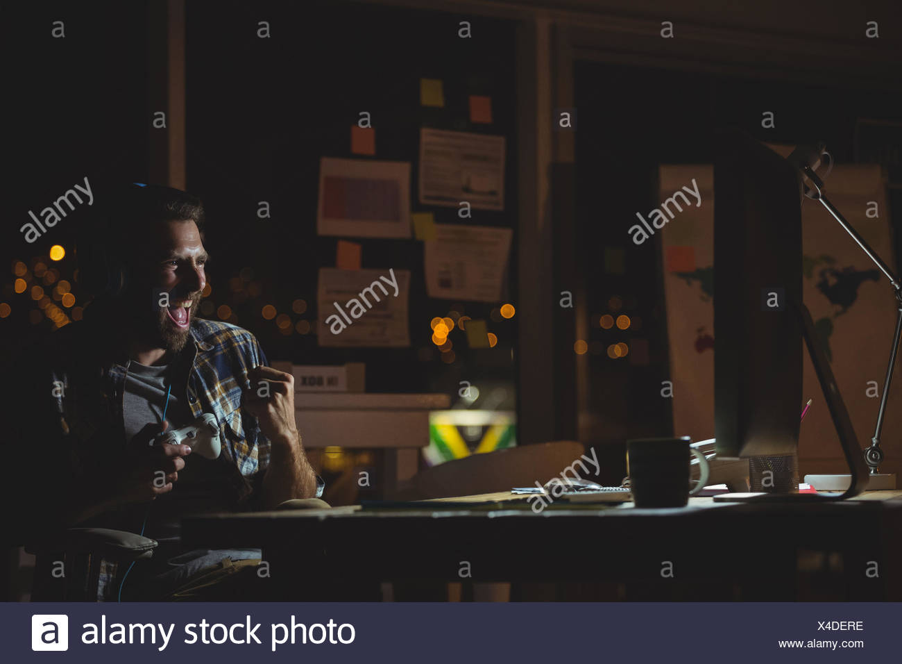 Businessman playing computer games at night - Stock Image