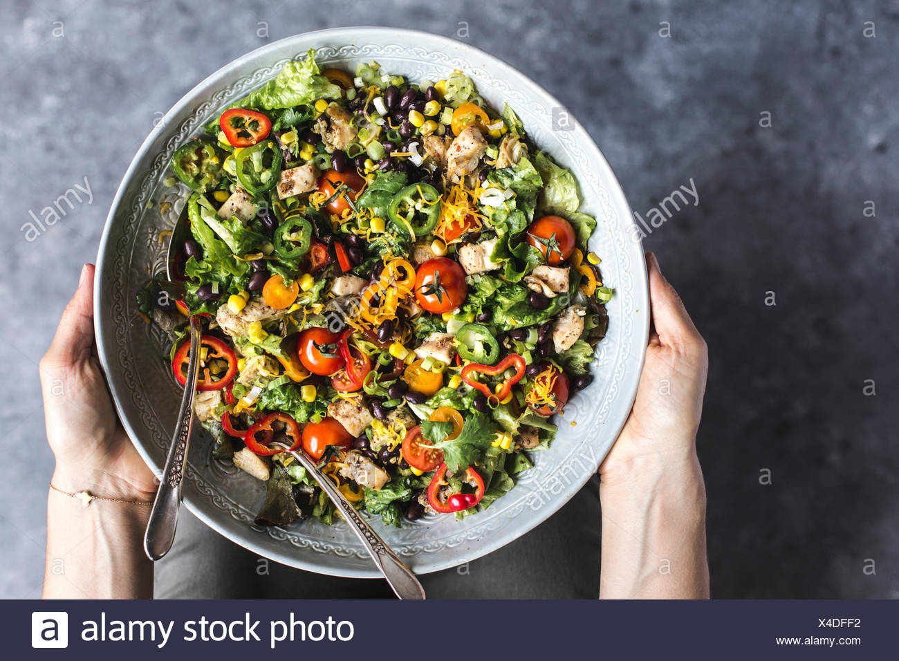 A large bowl of Southwestern Chicken Salad with Creamy Avocado Dressing in a woman's hands is photographed from the top view. - Stock Image