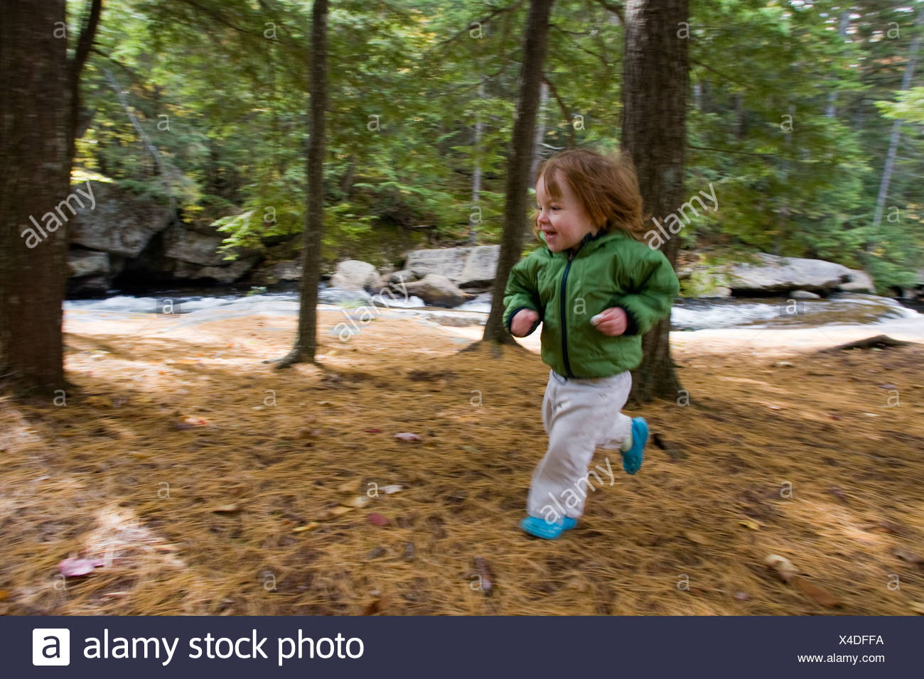 A young girl runs through the woods. - Stock Image