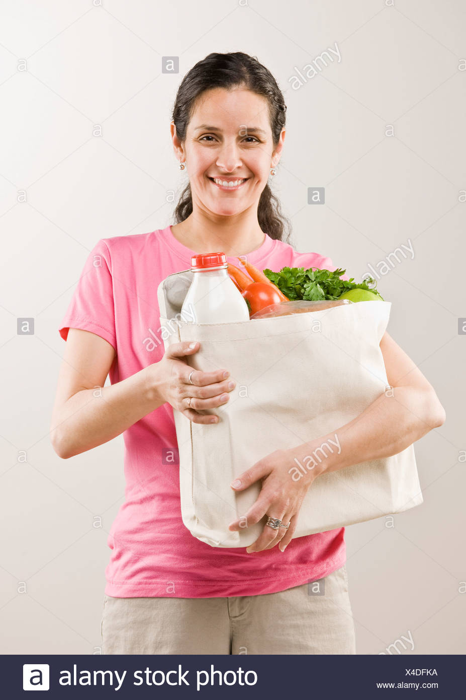 Woman carrying bag of groceries - Stock Image