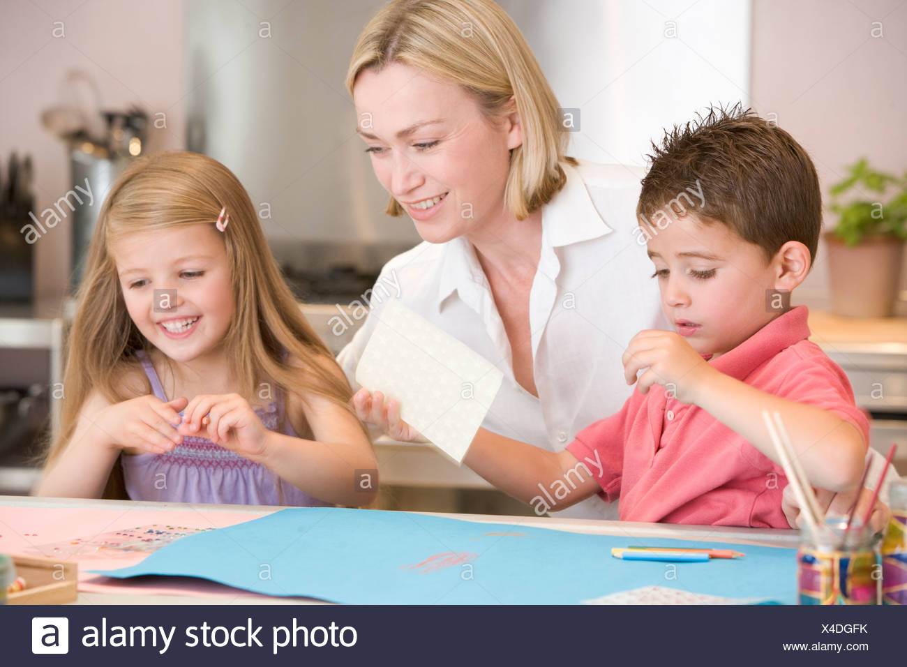 Woman and two young children in kitchen with art project smiling - Stock Image