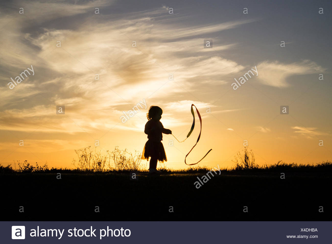 Silhouette of a girl playing with a ribbon - Stock Image