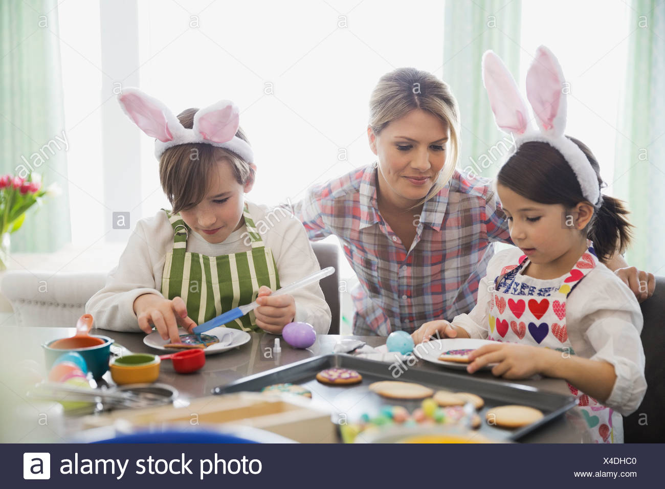 Mother with children decorating Easter cookies - Stock Image